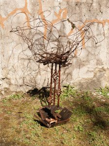 Welded steel sculpture of nest on pedestal