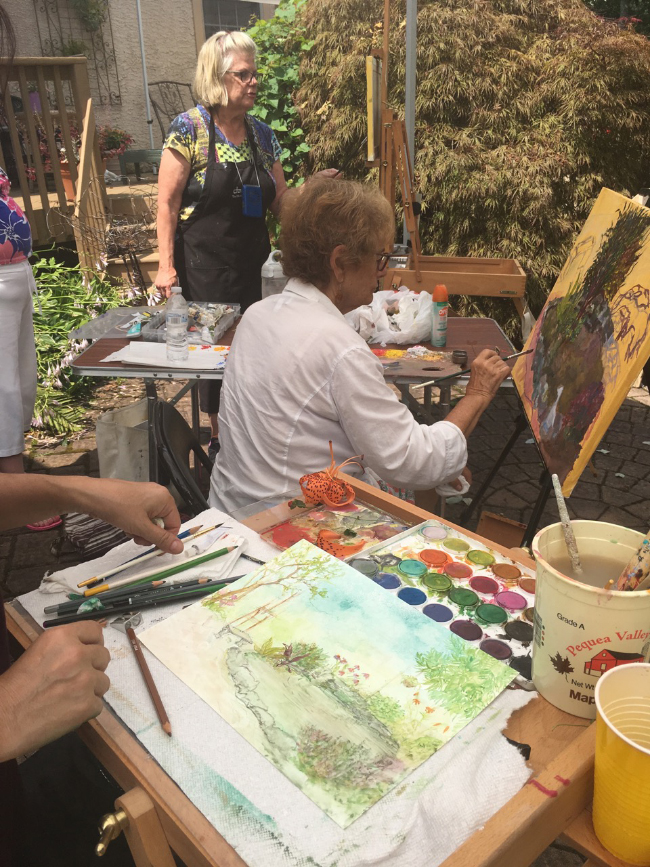 Side by side, Delona (here is her hand, her palette and her lovely watercolor), Joan (top) and Bobbi share some tips, feedback, suggestions and, shade under a tent.